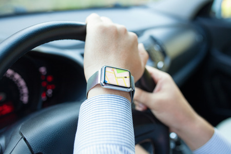 portables: Man hand in the car with watch and app navigation on the screen Stock Photo