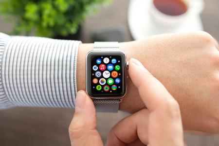 manzana: Alushta, Rusia - 1 septiembre 2015: la mano del hombre con el reloj de Apple y el icono de la aplicaci�n en la pantalla. Apple Seguir fue creado y desarrollado por la Apple inc.