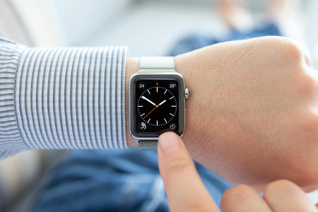 Alushta, Russia - September 24, 2015: Man hand with Apple Watch and dial on the screen. Apple Watch was created and developed by the Apple inc.
