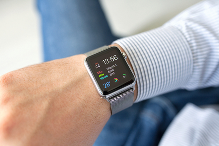 apple computer: Alushta, Russia - September 24, 2015: Man hand with Apple Watch in the home. Apple Watch was created and developed by the Apple inc.