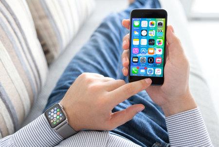 manzana: Alushta, Rusia - 24 septiembre, 2015: Mano del hombre con Apple Seguir sosteniendo iPhone. Apple Seguir fue creado y desarrollado por la Apple inc.