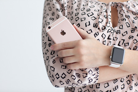 아루샤, 러시아 - 3 월 (22), 2015 아이폰 6 S 로즈 골드를 들고 손에 애플 시계와 여자입니다. 아이폰 6S와 시계를 만들어 애플 INC에 의해 개발되었다.