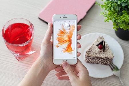 mujer con rosas: Alushta, Rusia - 25 de octubre 2015: La mujer abre el tel�fono iPhone6S oro rosa sobre la mesa. iPhone 6S Rosa de Oro fue creado y desarrollado por Apple inc. Editorial