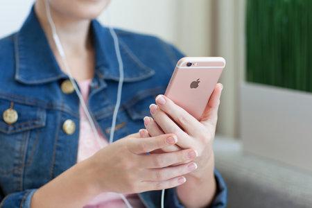 apfel: Alushta, Russland - 27. Oktober 2015: Frau mit Kopfh�rern in der Hand iPhone6S Rose Gold zu halten. iPhone 6S Rose Gold wurde von der Apple Inc erstellt und entwickelt.