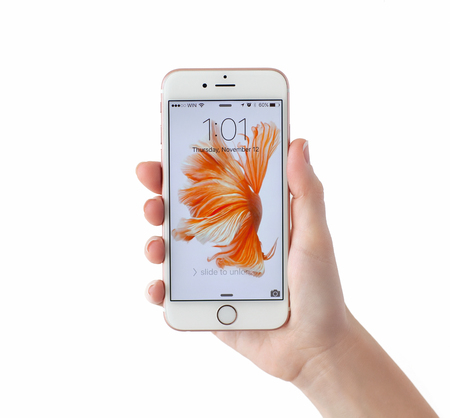 Alushta, Russia - November 12, 2015: Woman unlock iPhone6S Rose Gold in the hand on the white background. iPhone 6S Rose Gold was created and developed by the Apple inc.
