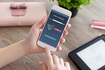 le mani femminili in possesso di telefono bianco con lo shopping online sullo schermo e e-rider sulla tabella delle donne