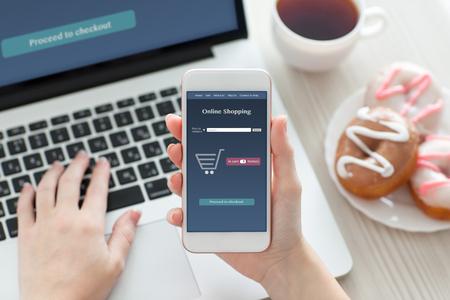 mains des femmes tenant un téléphone blanc avec des achats en ligne à l'écran sur une table avec un ordinateur portable