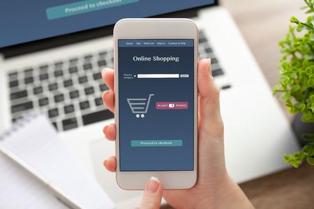 Femmina mano che tiene telefono bianco con lo shopping online sullo schermo su un tavolo con un taccuino Archivio Fotografico