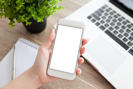 phone isolated: female hand holding a white phone with isolated screen on a table with laptop