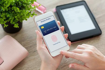 여성의 손을 들고 흰색 전화 애플 리케이션 모바일 테이블에 여성 지갑에 지갑