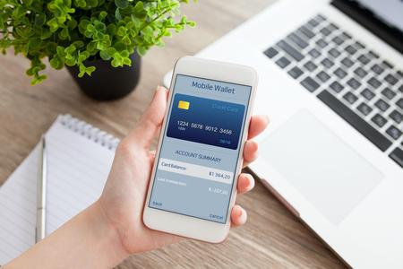 Mano femmina in possesso di un telefono bianco con app mobile wallet sullo schermo su un tavolo con il computer portatile