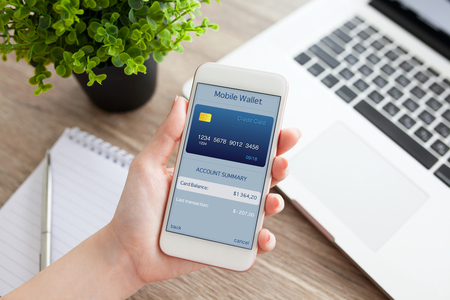 vrouwelijke hand met een witte telefoon met app mobiele portemonnee op het scherm op een tafel met laptop