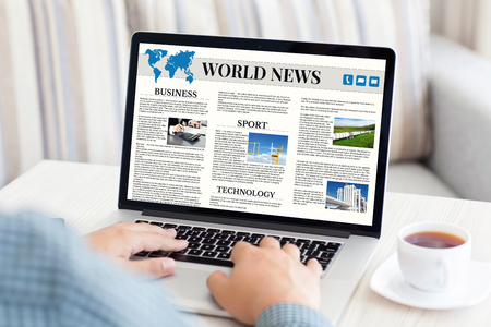 man with laptop: man typing on a laptop keyboard with world news site on the screen in the room Stock Photo