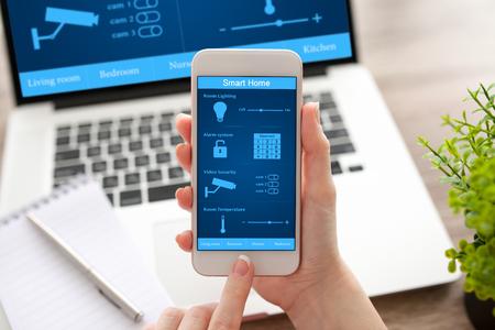 mains femme tenant téléphone blanc et ordinateur portable avec app maison intelligente sur l'écran