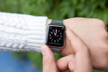 hour hand: Alushta, Russia - October 14, 2015: Man hand and Apple Watch with time on the screen. Apple Watch was created and developed by the Apple inc.