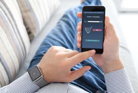 man lying on the sofa with a smart watch and holding phone with online shopping on the screen