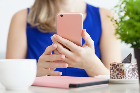 portables: woman in blue dress in the cafe holding pink phone