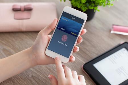 manos de una mujer que sostiene el teléfono blanco con toque de tarjetas de débito y pagar en la pantalla