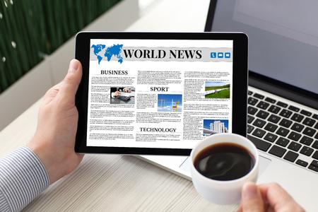 화면 및 커피 근처 노트북에 세계 뉴스와 태블릿 컴퓨터를 들고하는 남자