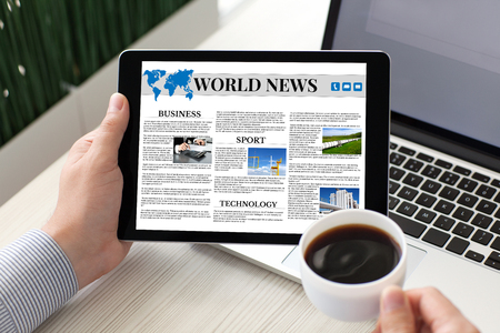 man holding tablet computer with world news on screen and coffee near notebook Imagens