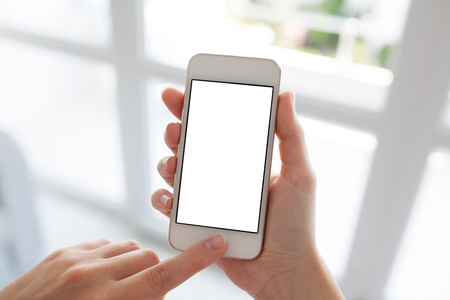 Women hands holding white phone with isolated screen on background window