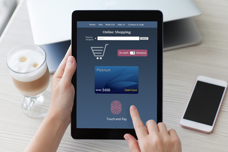 woman hands holding tablet PC computer with online shopping touch pay over notebook and phone