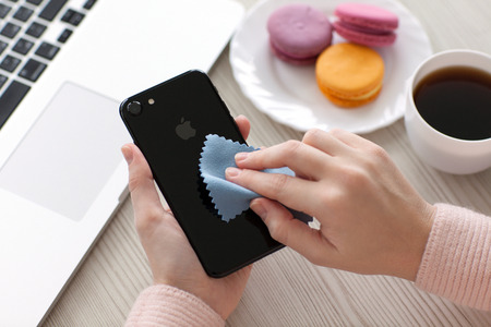 10 fingers: Alushta, Russia - November 19, 2016: Woman hand holding iPhone 7 and cleaning it. iPhone 7 Jet Black was created and developed by the Apple inc.