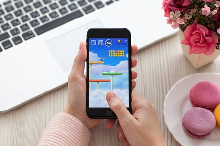 games hand: Alushta, Russia - November 19, 2016: Woman hand holding iPhone 7 Jet Black with game Super Mario Run in the screen. Games Super Mario Run was created and developed by the Nintendo. Editorial