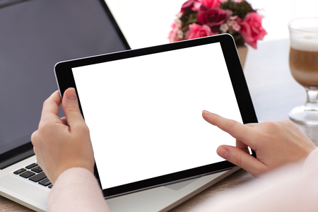 woman hands holding tablet computer with isolated screen on laptop background Stock Photo