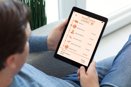 man in jeans on sofa holding tablet computer with app tracking delivery package