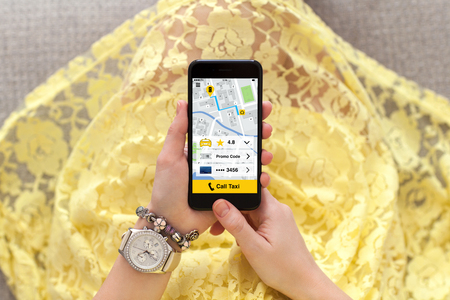 woman in yellow dress with jewelry holding phone application call taxi on screen