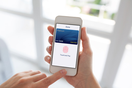 Women hands holding white phone with debit card app touch pay on screen