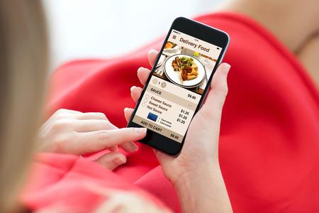 mujer en el teléfono del tacto con vestido rojo con pantalla de alimentos de entrega de aplicaciones
