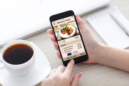 Manos de las mujeres que sostienen el teléfono con la pantalla de la entrega de alimentos aplicación sobre el escritorio en la oficina