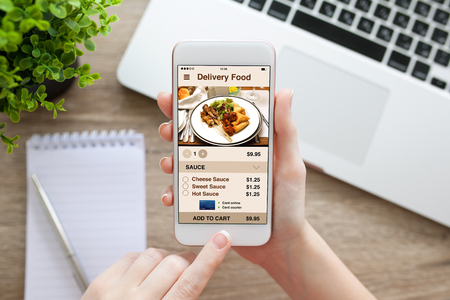 female hand holding white phone with app delivery food screen and laptop Stock Photo