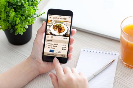 여자 손 데스크 위의 화면에 애플 리케이션 배달 음식과 전화를 들고