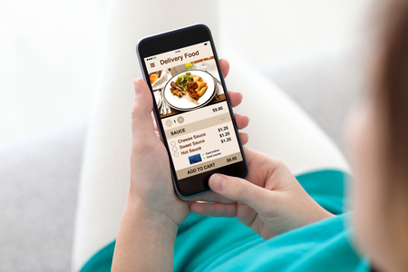 woman sitting on sofa and holding phone with app delivery food screen
