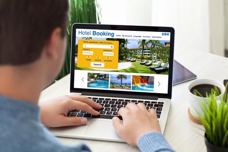 Homme dactylographiant clavier portable avec recherche en ligne hôtel de réservation à l'écran dans la chambre