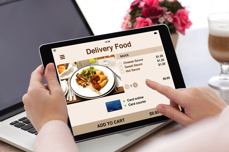 phone business: woman hands holding tablet computer with app delivery food on screen and laptop