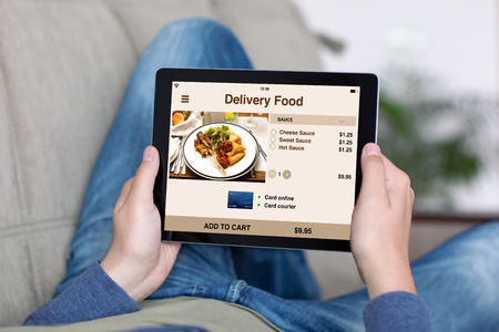 media gadget: man lying on sofa and holding tablet with app delivery food on screen