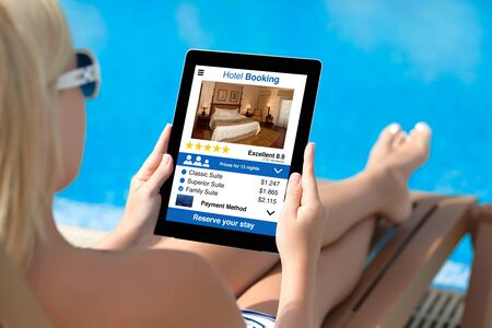 woman on sun lounger by pool holding tablet with app hotel booking screen photo