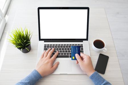 남자 손 사무실 책상에 전화를 통해 격리 된 화면으로 신용 카드 노트북을 들고