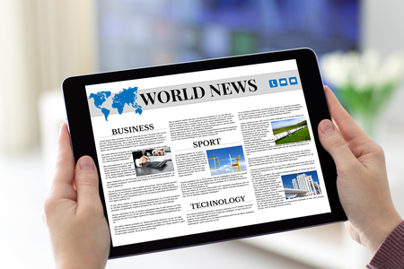 Female hands holding tablet with app world news screen in room house