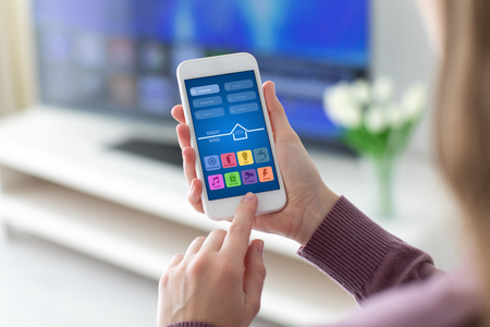 Female hands holding phone with app smart home screen in room house