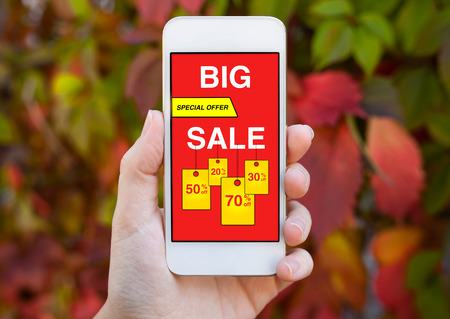 female hand holding white phone with big sale screen on background colored leaves trees