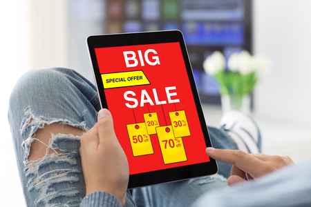 man jeans holding tablet with big sale screen in room