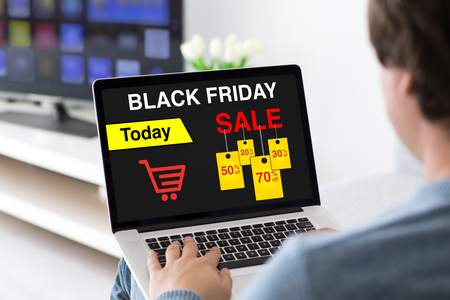 man typing on laptop keyboard with sale black friday on screen in room
