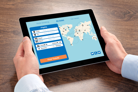 man hands holding tablet computer with application search air ticket on screen