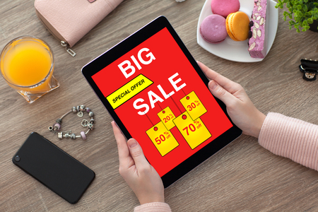 woman hands holding tablet with big sale screen on desk with phone