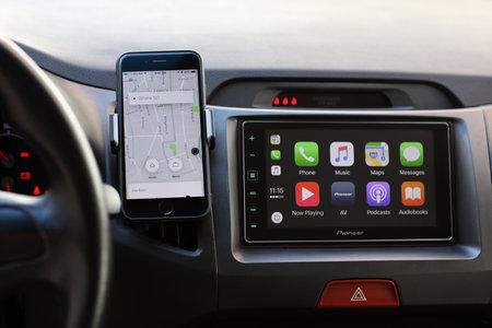 Aluschta, Russland - 20. April 2017: iPhone mit Anwendung Taxi Uber und Auto spielen auf dem Bildschirm. Das iPhone wurde von Apple Inc. erstellt und entwickelt.